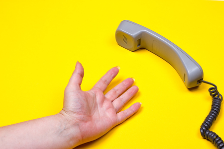 phone cord: female hand lies next to the telephone receiver on the wire on a yellow background