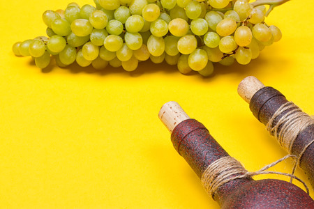 bottle of white wine with grapes on a yellowbackground