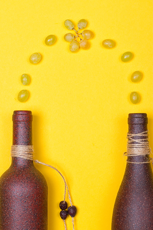 White grapes are poured into stone bottles on a yellow background Stock Photo