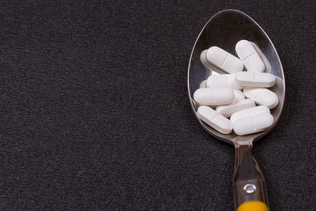 Assorted pharmaceutical medicine pills, tablets and capsules on wooden spoon. black background 版權商用圖片