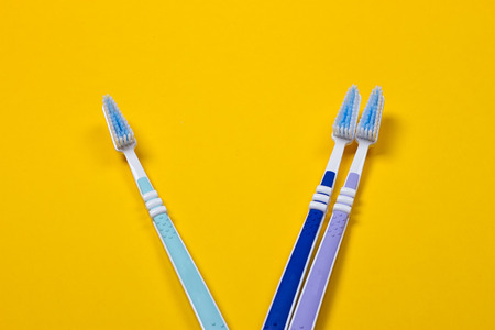 three Toothbrushes on the yellow background. Top view Stock Photo