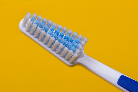 Toothbrushes on the yellow background. Top view