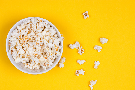 Bowl of Delicious Popcorn spilling onto a yellow background