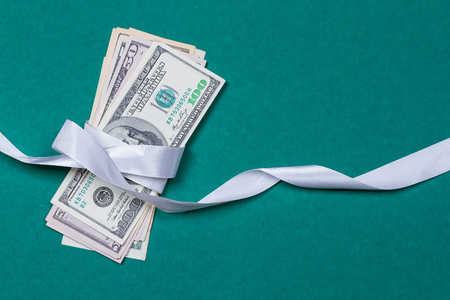 dollars in gift wrapping gift concept. on a green background