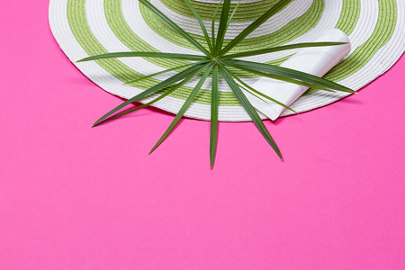 flip flops: Beach hat and coconut leaves on pink background Stock Photo