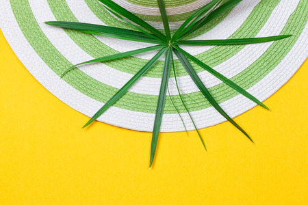 flip flops: Beach hat and coconut leaves on yellow background Stock Photo