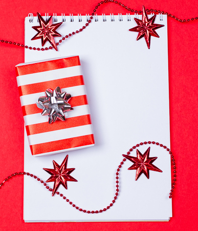 Holiday decorations and notebook and gift on red background Stock Photo
