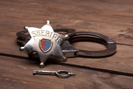 old sheriff badge and handcuffs Stock Photo - 8222235