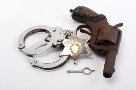 old sheriff badge, handcuffs and gun photo