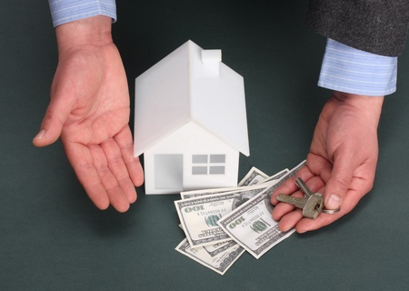 parts of hands with house and money photo