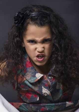 pretty cute swarthy  little brunette angry girl on black background frowning photo