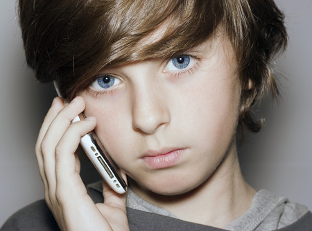 blue eyes: insightful look blue eyes boy face with telephone