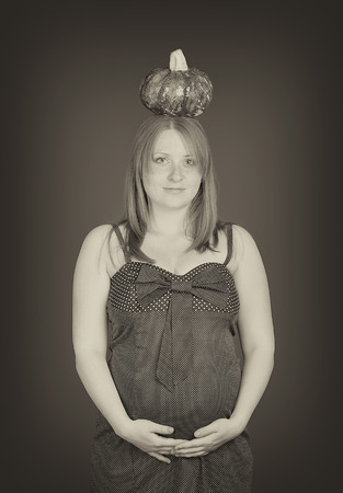 b w: pregnant woman and a pumpkin on her head Stock Photo
