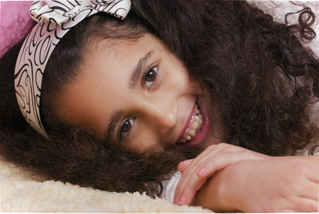 swarthy: Smiling child brunette swarthy girl lying in the bed