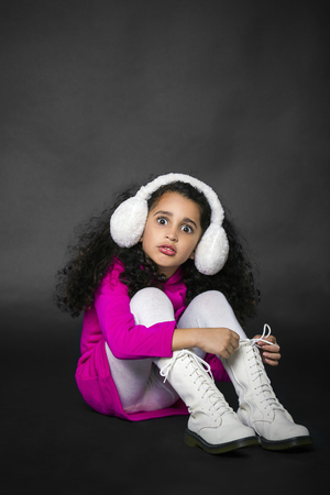 sitting pretty: pretty little girl sitting on the floor in white boots