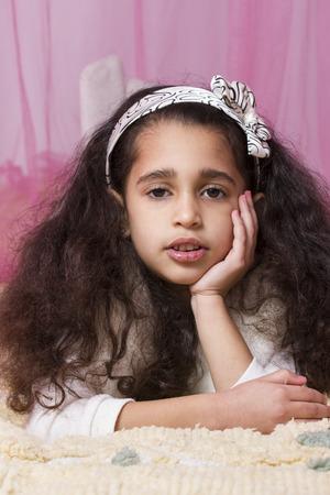 swarthy: Little cute swarthy brunette girl on pink background. Cartoon