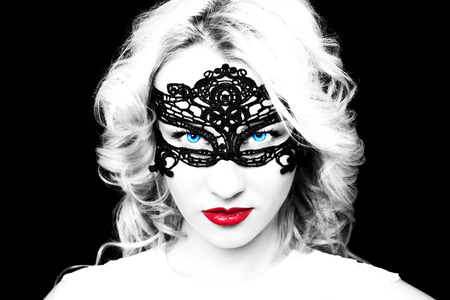 bdsm: Beautiful fashion model girl with blond hair in mask.Portrait of glamour woman with bright makeup isolated on black background.