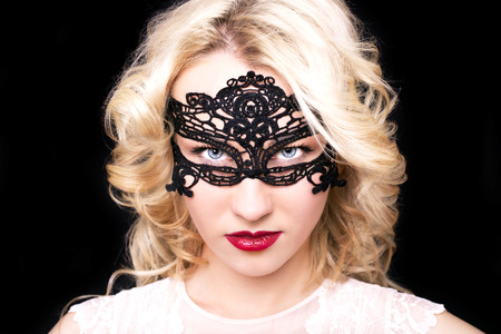 Beautiful fashion model girl with blond hair in mask.Portrait of glamour woman with bright makeup isolated on black background.