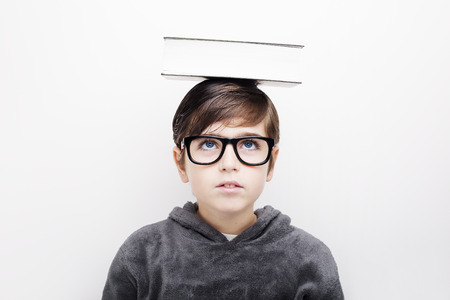Portrait of a little handsome boy kid in eyeglasses with book on head. Isolated white background Standard-Bild