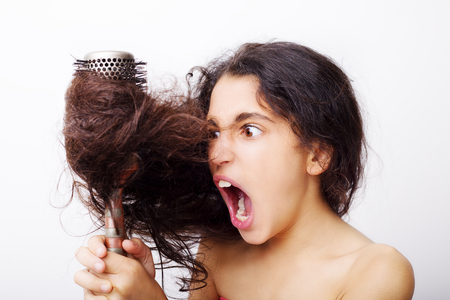 hairdresser: Hair care concept with portrait of girl brushing her unruly, tangled long hair isolated on white