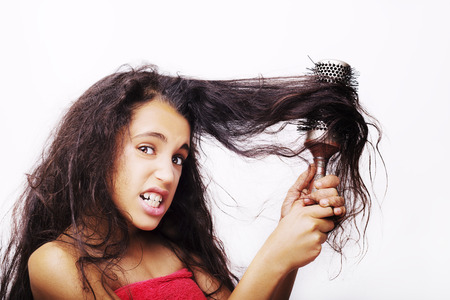 Hair care concept with portrait of girl brushing her unruly, tangled long hair isolated on white