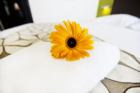 comfortable: a fresh white towel with yellow flower on the bed Stock Photo