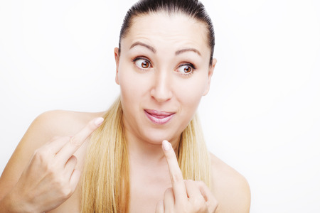 Portrait of a blonde girl showing middle fingers, isolated on a white background Stock Photo