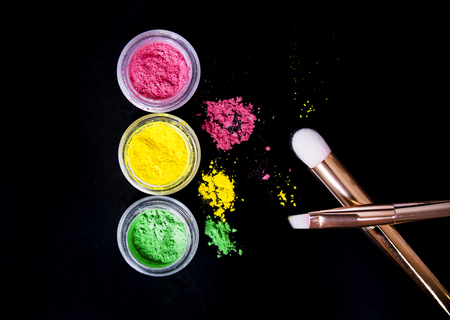 gloss: Set of colorful mineral eye shadows with brushes on black background