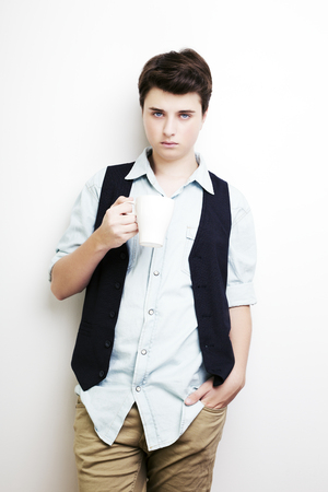Coffee break. Confident young handsome man in jeans shirt holding cup with hot drink