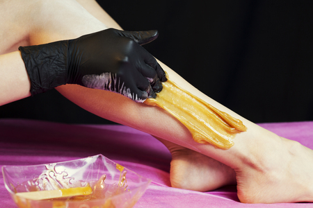 Sugaring epilation with liquate sugar at legs on black background