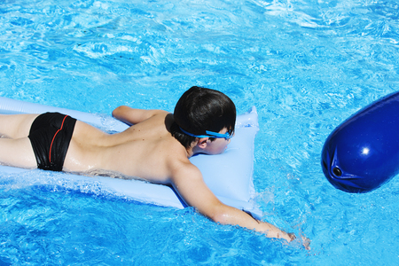 Activities on the pool, children swimming and playing in water