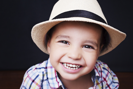 Emotional cute boy checkered shirt and straw hat