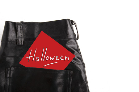 Halloween on white paper in the pocket of black leather trousers Stock Photo