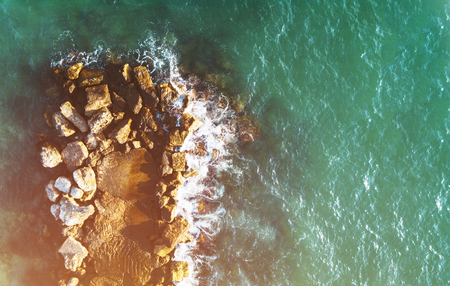 Aerial photo above rock outcrop in crystal clear warm water. Coast of Mediterranean sea in Israel