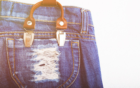 Detail of a white suspenders on vintage jeans close-up Stock Photo