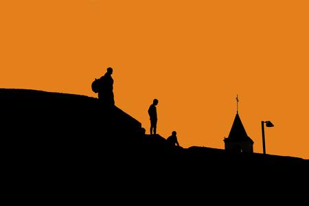 Schattenbilder von Leuten auf dem Dach von Häusern. Schwarzweiss-Foto. Silhouetten und Konturen.