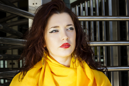 Pensive beautiful girl with a yellow scarf around her neck, looking into the distance