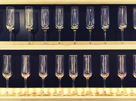 Empty glasses on shelf in restaurant. Lot clear wine glasses on high rack in row on rack in the store or supermarket