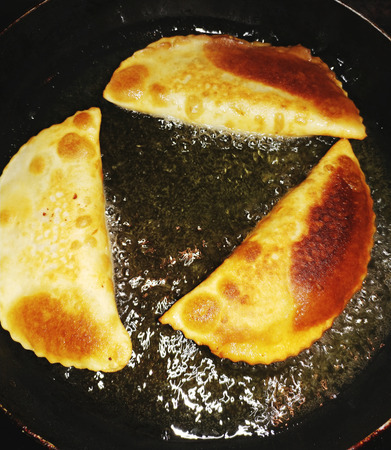 Cheburek with meat frying in oil in frying pan. Chebureks. Cook at home.  Stock Photo