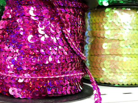 Background sequin.glitter surfactant. Holiday abstract glitter background with blinking lights. Fabric sequins in bright colors. Fashion fabric glitter sequins.