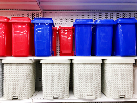 plastic multicolored waste buckets stand on store shelves sold Stock Photo