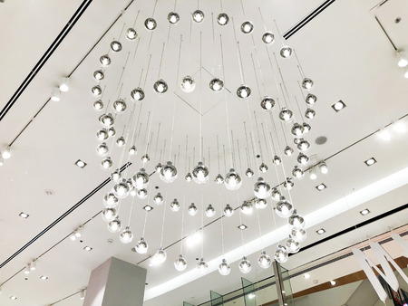 Expensive interior. Large electric chandelier made of transparent glass beads. White ceiling decorated with stucco molding