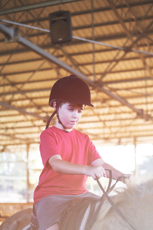 Portrait of little boy riding a horse. First lessons of horseback riding Stock Photo - 99569668