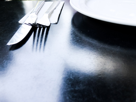 empty white plate on black table with knife and fork. Imagens