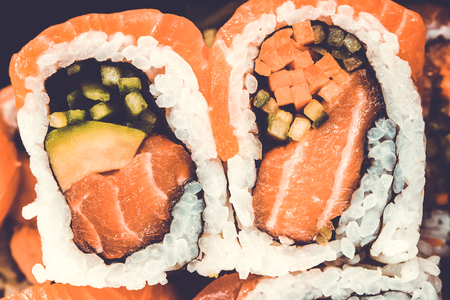 Sushi roll from salmon in assortment on black background. A traditional dish of Japanese cuisine
