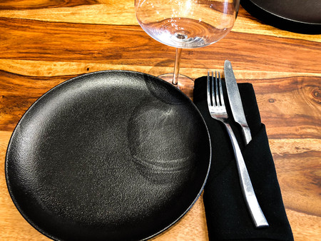elegant table setting using a glass, plates, napkins with a fork and knife.