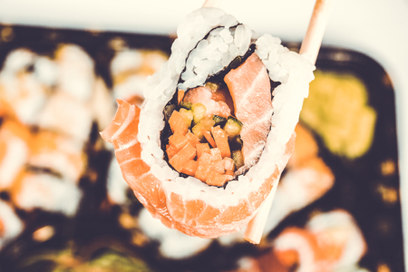 Sushi rolls holding by chopsticks. A traditional dish of Japanese cuisine