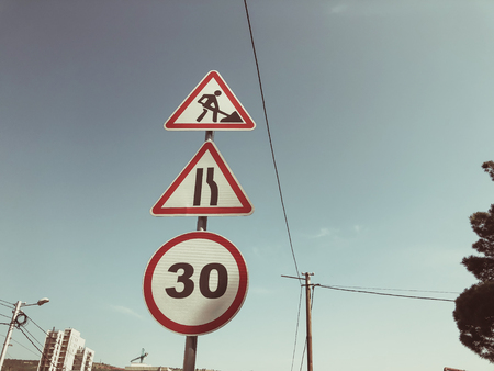 Traffic sign against the sky : Be careful road works are being carried out. Speed: 30 km  h