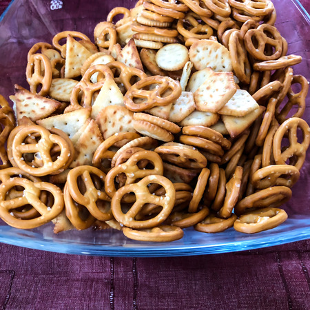 Mix of salty snacks (crackers and pretzels) in glass bowl on purple background. Close up shot.