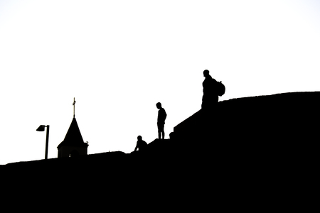 Silhouettes of people on the roof of houses. Black and white photo. Silhouettes and Contours.